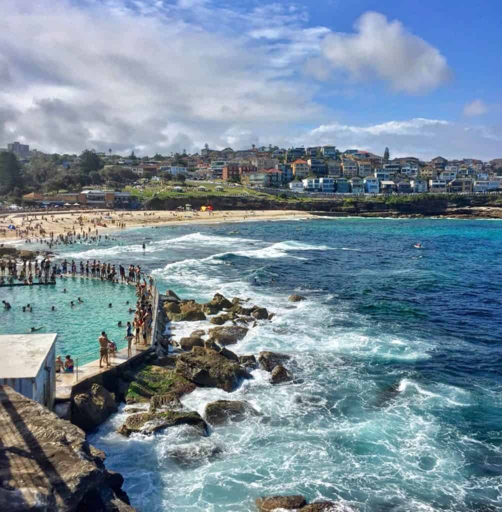 people surfing and sunbathing on a sandy beach and an ocean pool