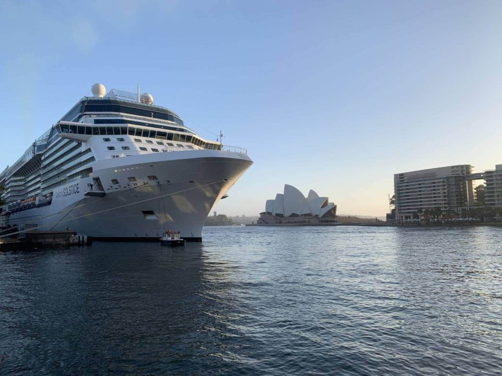 cruise ship docked in port with sydney opera house in the background