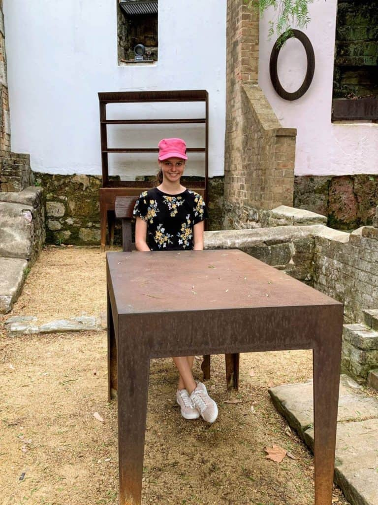 foundations in a park with a girl sitting on a chair and table
