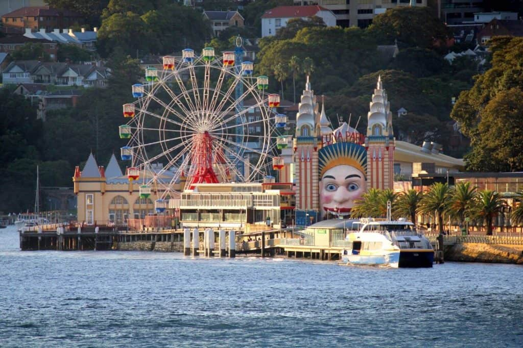 an amusement park with a big smiley face as the entrance on the harbour with a ferris wheel