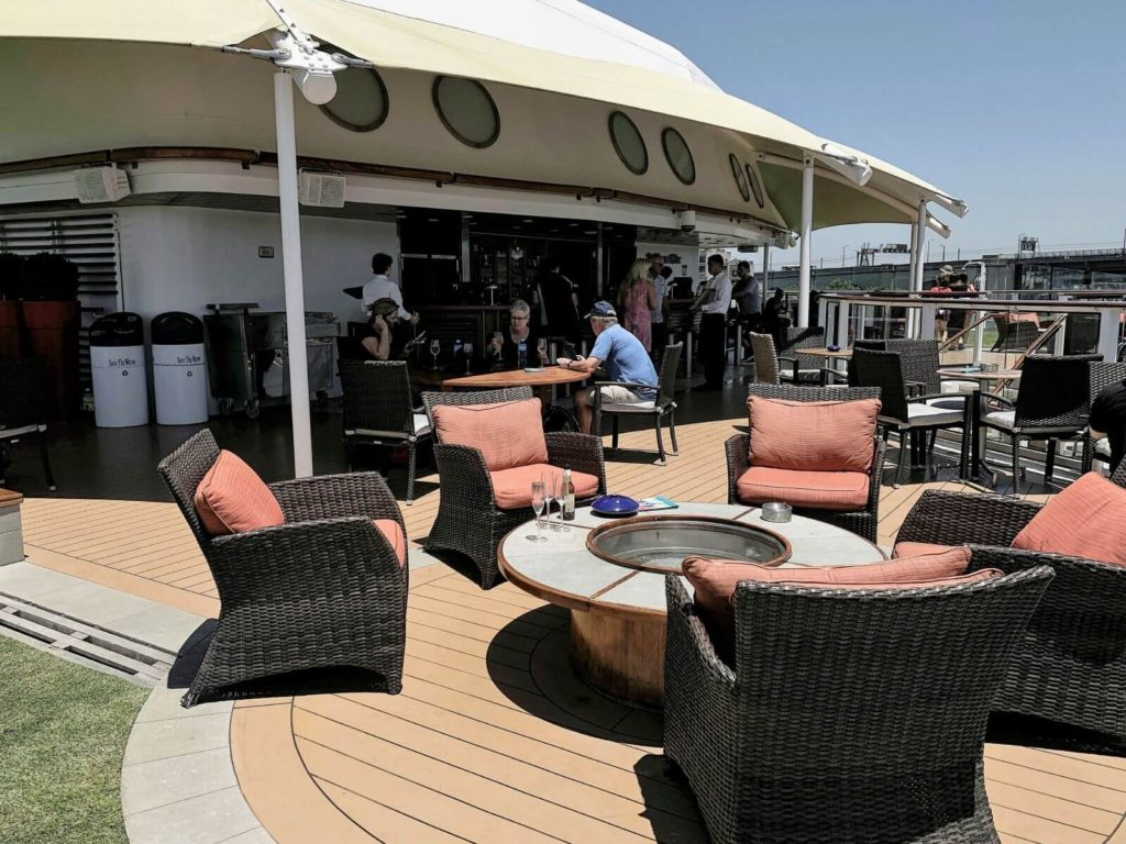 an outdoor bar with seating at the back of a ship