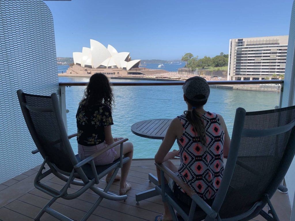 two people sitting on a cruise ship balcony looking at the sydney opera house