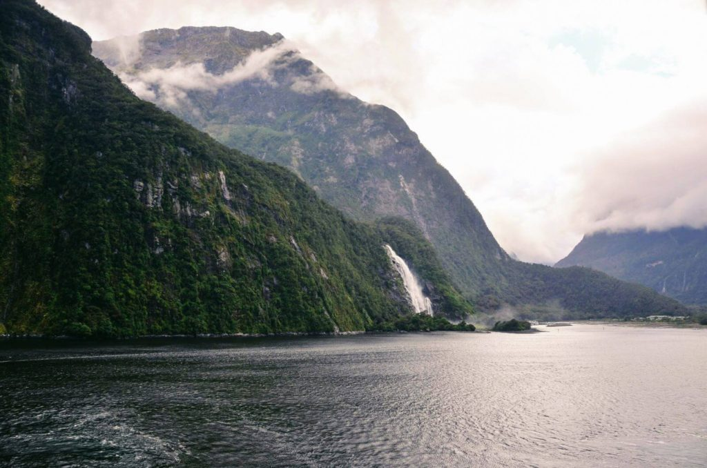 a waterfall flowing down from the mountains into a fjord