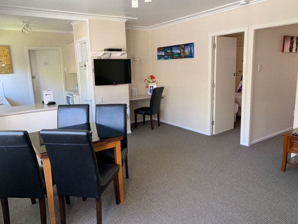 best western in rotorua lounge area with dining table and chairs plus desk and television