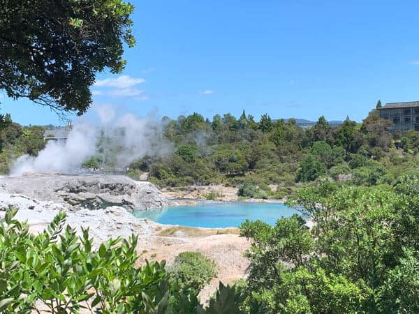 A bright blue lake surrounded by rock and green trees with steam coming from it