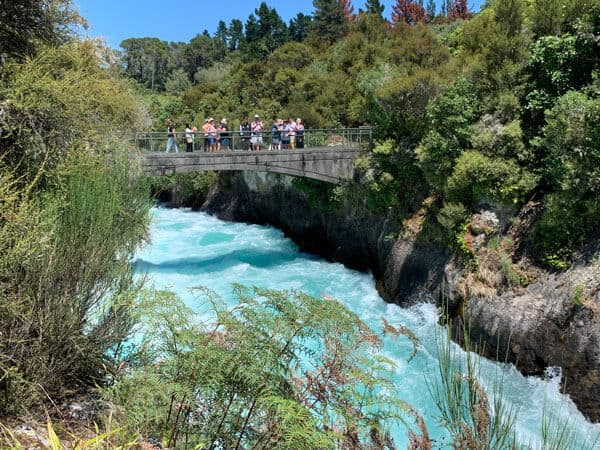 footbridge over the turquoise waters of huka falls with people on the bridge looking at the water