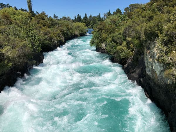 turquoise waters fast flowing down the river towards huka falls