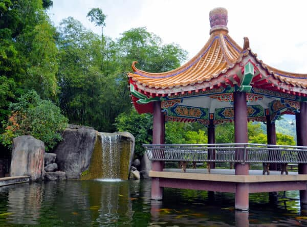 a chinese gazebo on a large goldfish pond with a waterfall cascading into it