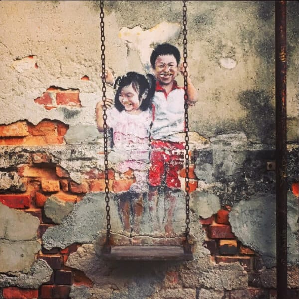street art of a girl and a boy standing on a swing