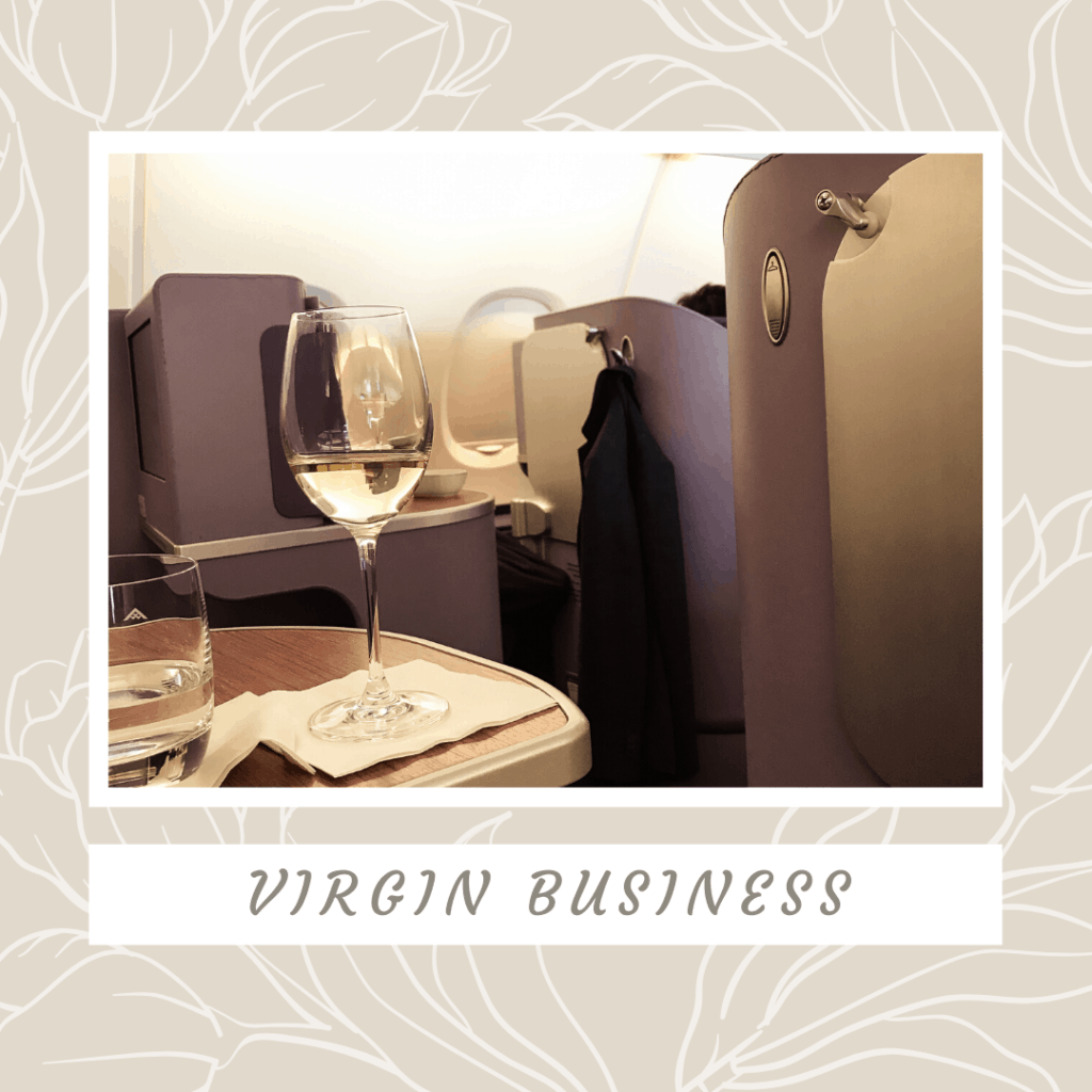 business class cabin on an aeroplane with purple fully flat lie down beds