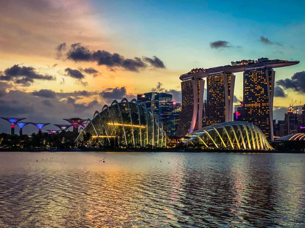 sun setting over modern buildings with lights travel resources