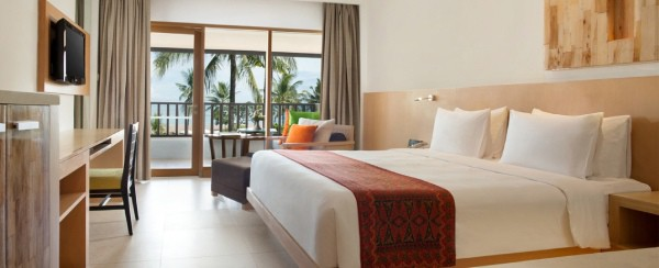 hotel room with king bed and archair with balcony overlooking palm trees with view of ocean