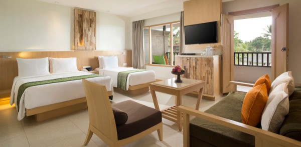 a big room hotel suite with beds and tropical look