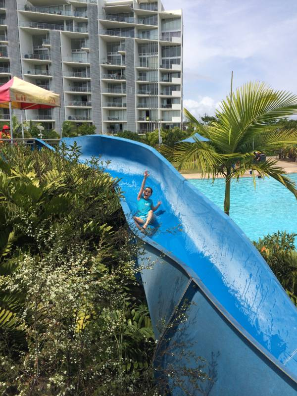a child on a blue water slide at a lagoon