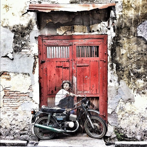 street art of a red door and a motorbike