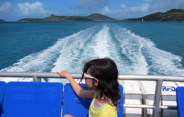 girl looking out to see on a ferry with an island in the background