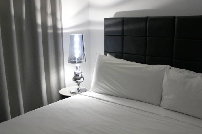bed in one of the orchard road family hotels and lamp on bedside table