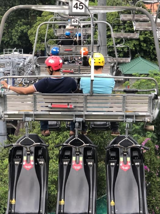 people on a skyline with luge capsules