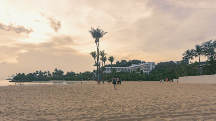 sandy beach with people walking with a hotel in the background