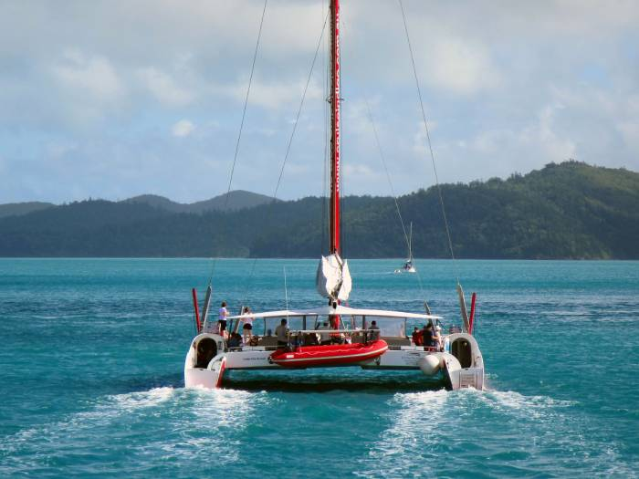 red and white catamaran sailing with people onboard looking out to the ocean