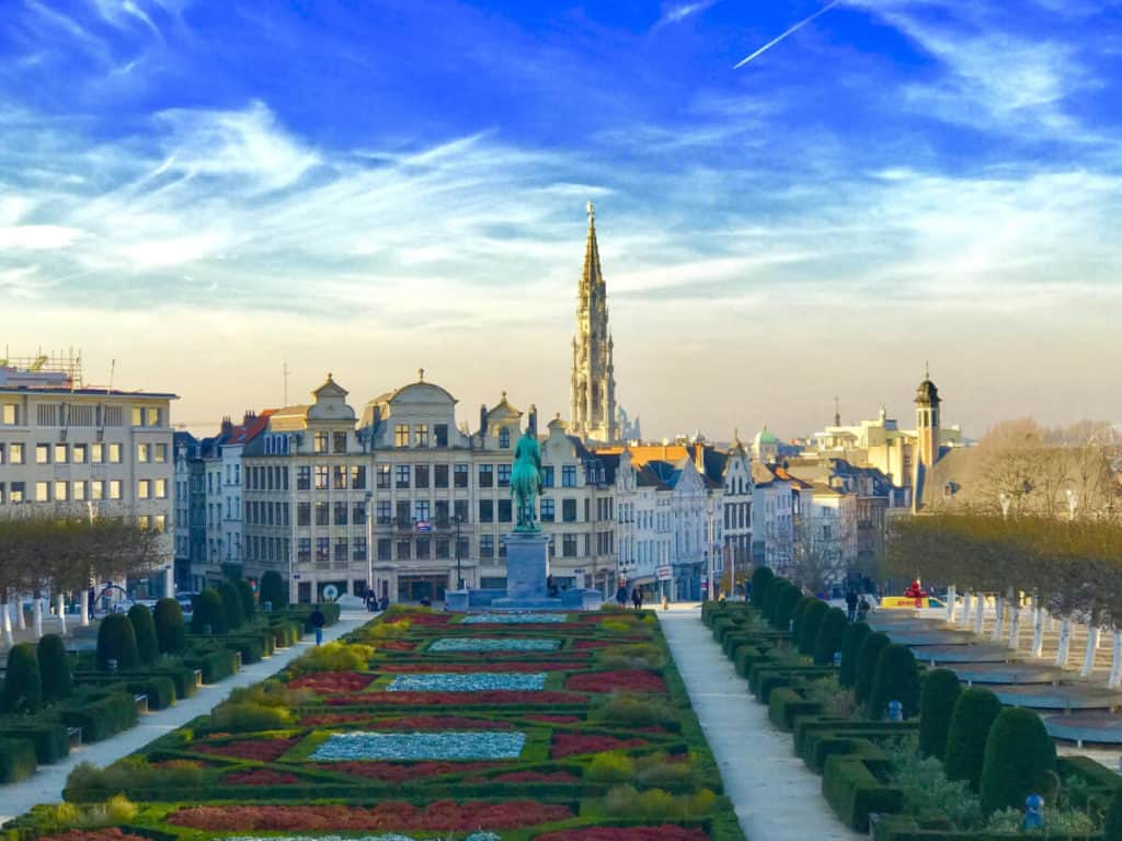 a big city with old buildings and a carpet of flowers and statues