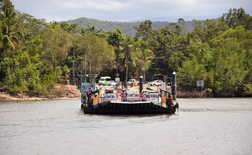 a cable ferry with cars crossing a river with rainforest in background