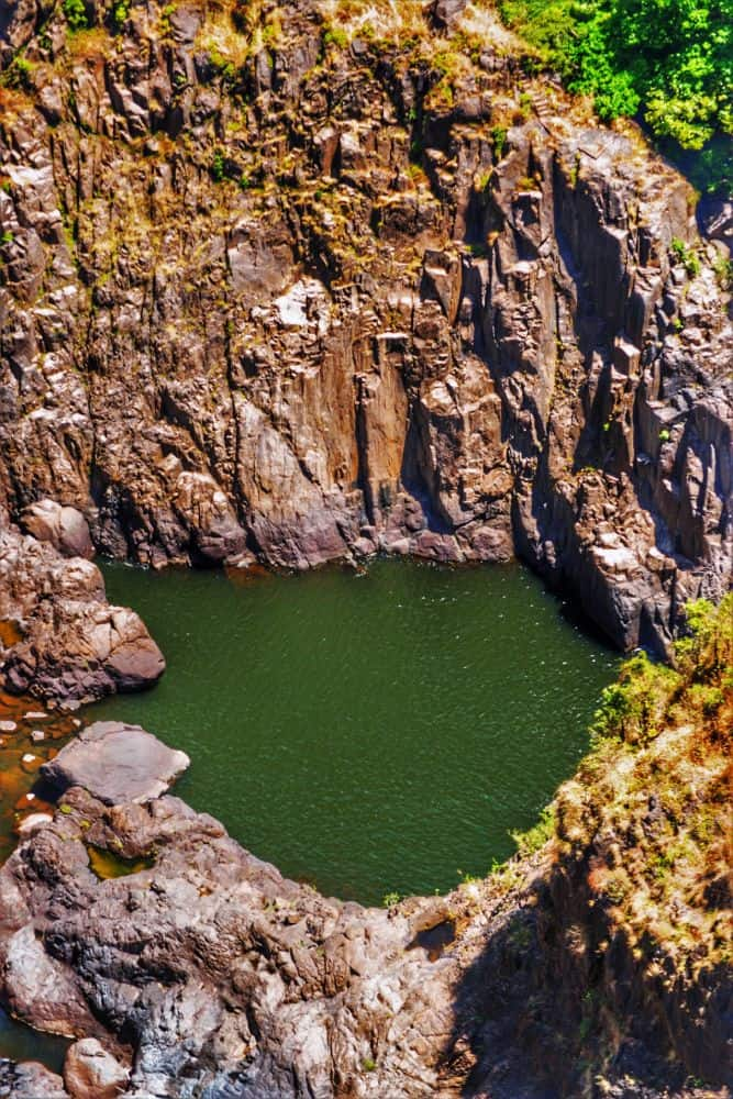a huge granite crater with a lake covered in green weed surrounded by rainforest