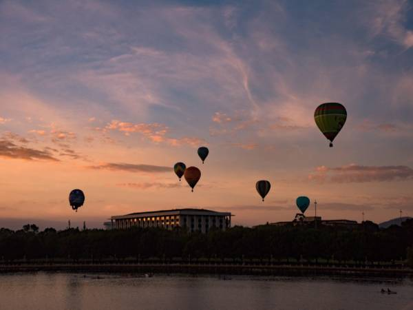hot air balloons over city at sunrise